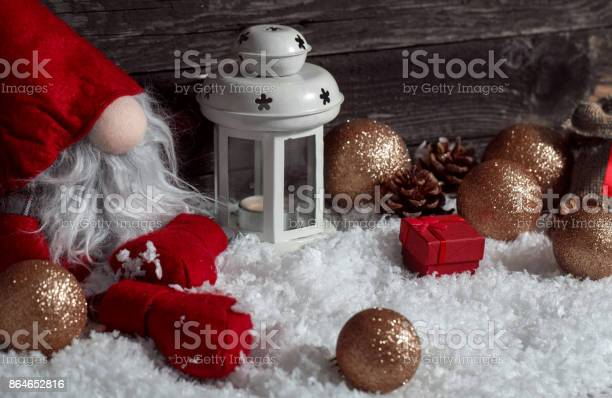 Photo of Funny Christmas dwarf on snow with Christmas decorative