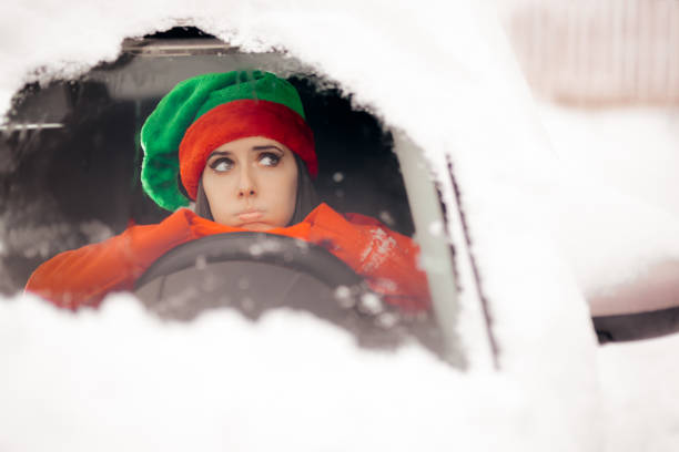funny christmas girl driving through the snow on bad weather - car chill foto e immagini stock