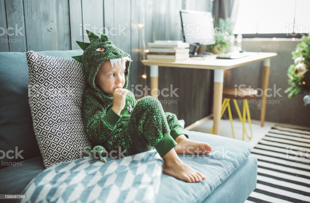 Funny Christmas morning at home Boy celebrating Christmas at home, he sitting on sofa  and enjoy in holidays, boy wears costume 4-5 Years Stock Photo