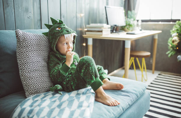 Funny Christmas morning at home Boy celebrating Christmas at home, he sitting on sofa  and enjoy in holidays, boy wears costume costume stock pictures, royalty-free photos & images