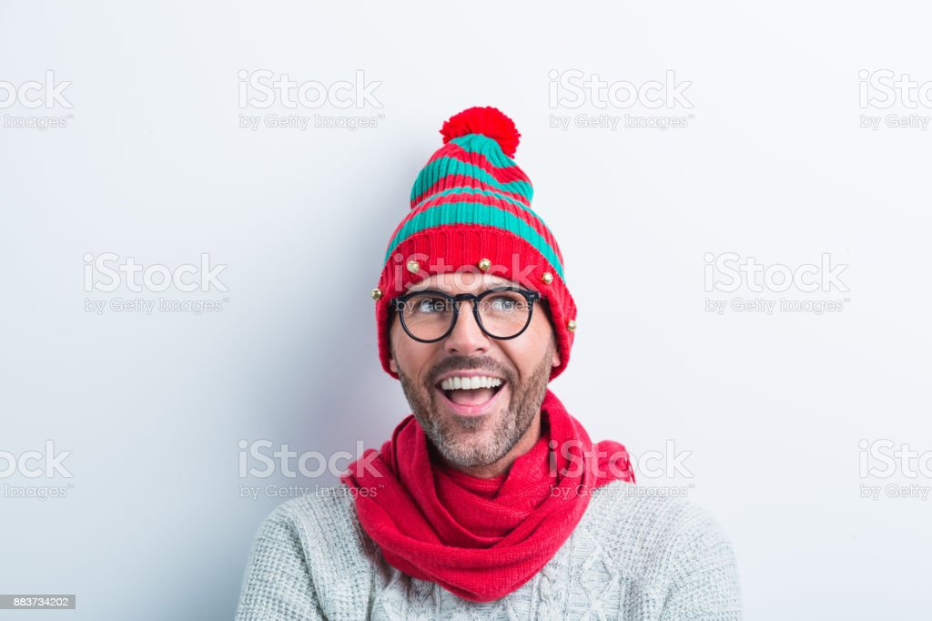 Funny christmas portrait of nerdy man wearing elf cap Funny christmas portrait of man wearing elf cap and red scarf. Surprised man wearing winter sweater against white background. 35-39 Years Stock Photo