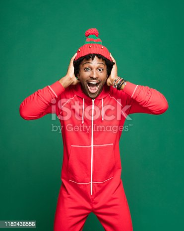 Funny Christmas portrait of young afro American man wearing red pajamas and woolen hat, laughing at camera with head in hands. Studio shot against green background.