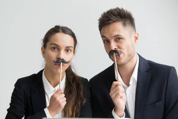 compañeros divertidos haciendo caras tontas con bigote falso, retrato de disparo en la cabeza - ironía fotografías e imágenes de stock