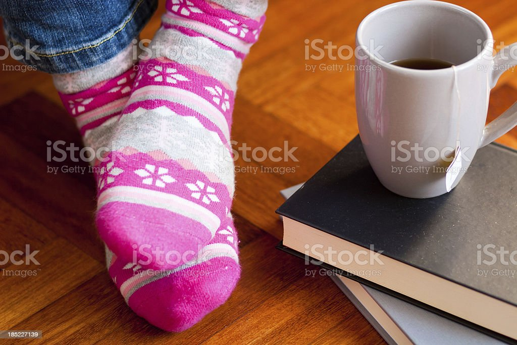 Funny colored socks with cup of tea and books. stock photo