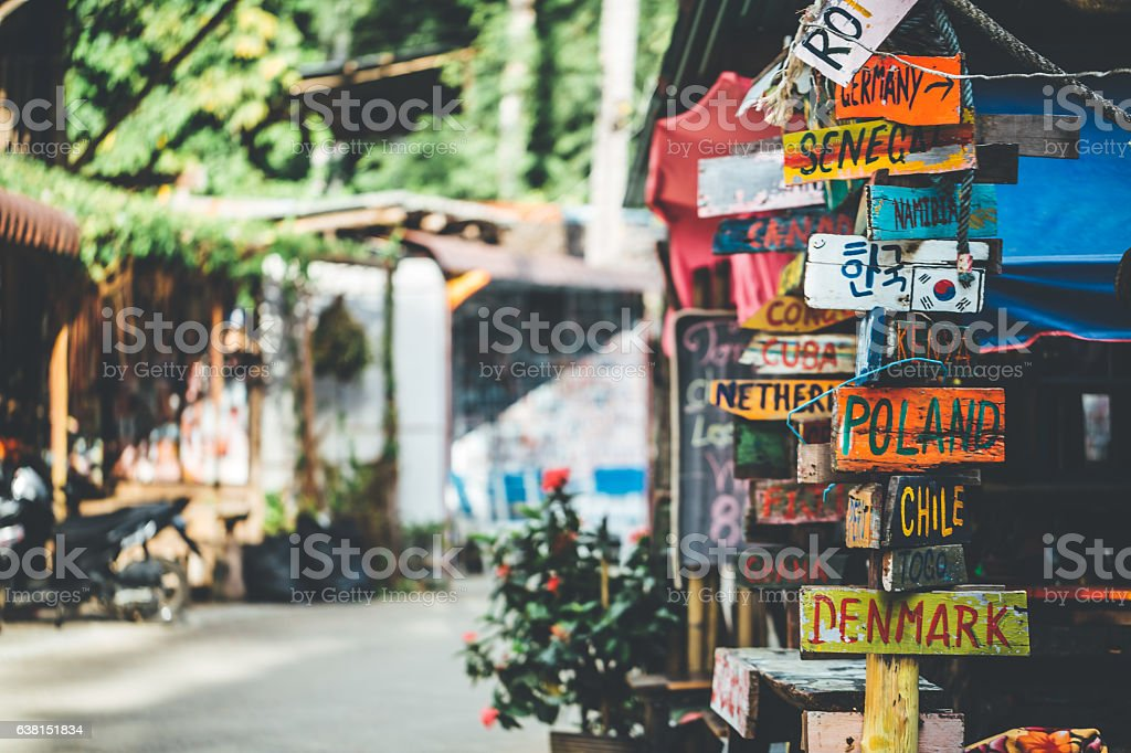 Funny colorful signpost to different countries around the world bildbanksfoto