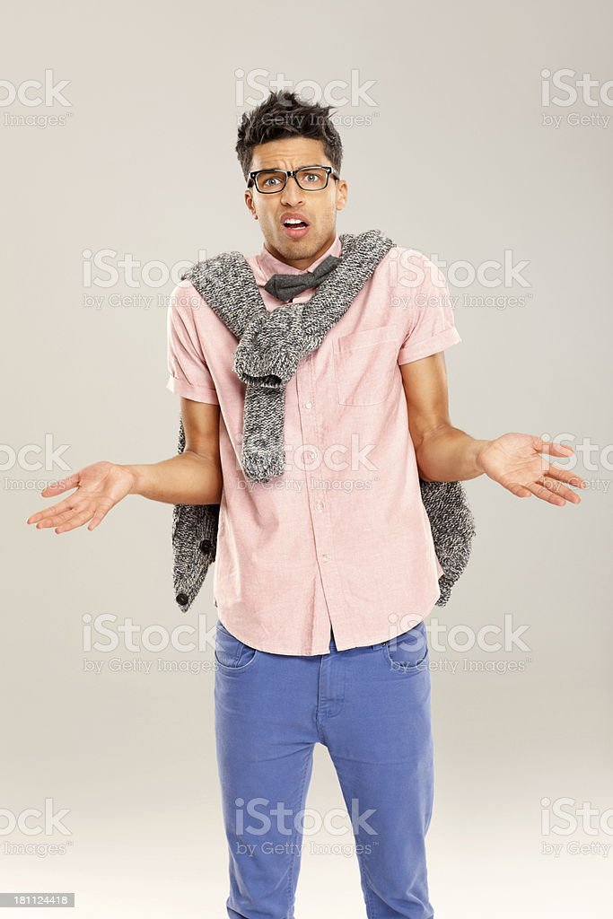 Funny confused nerdy guy on grey royalty-free stock photo