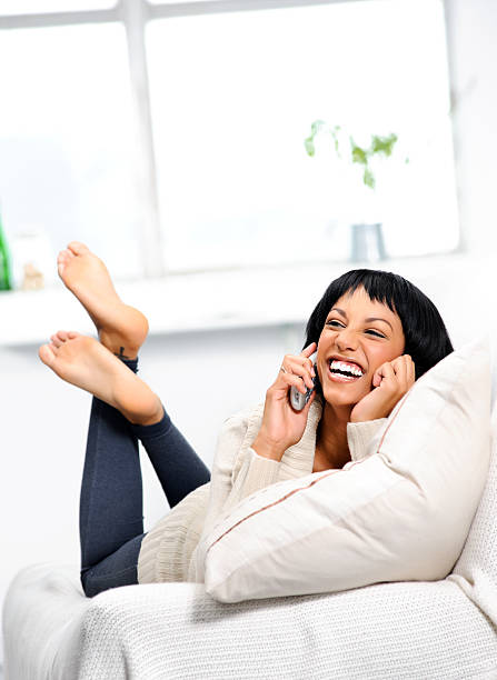 Funny conversation Cute indian girl laughing on the couch while on the telephone cordless phone stock pictures, royalty-free photos & images