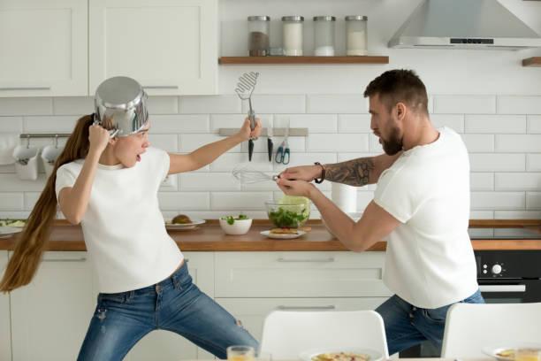 grappige paar plezier vechten met keukengerei koken t - couple fighting home stockfoto's en -beelden