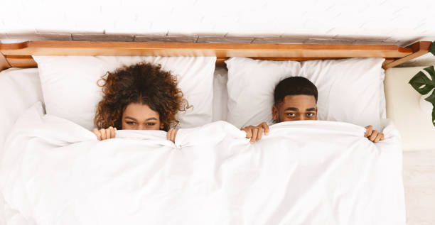 Funny couple hiding under white blanket in bed Funny millennial african-american couple hiding under white blanket in bed, top view couple in bed stock pictures, royalty-free photos & images