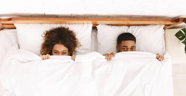 lustiges paar versteckt sich unter weißer decke im bett - sex sexuelle themen stock-fotos und bilder