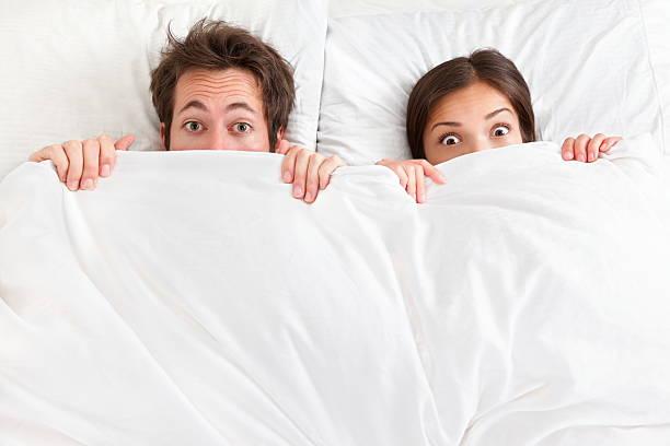 lustige paar im bett - marvel schlafzimmer stock-fotos und bilder