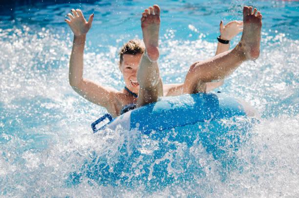 casal engraçado tomar uma água rápida passeio em um flutuador de salpicos de água. conceito de férias de verão. - organismo aquático - fotografias e filmes do acervo