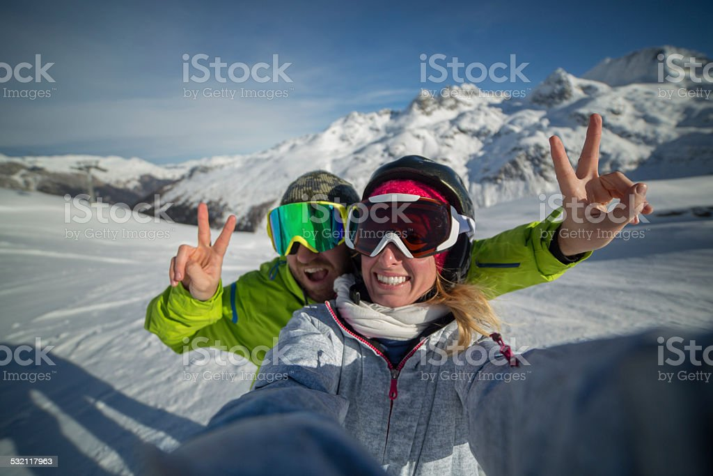 Young happy couple on ski slopes at the top of snow capped mountains...
