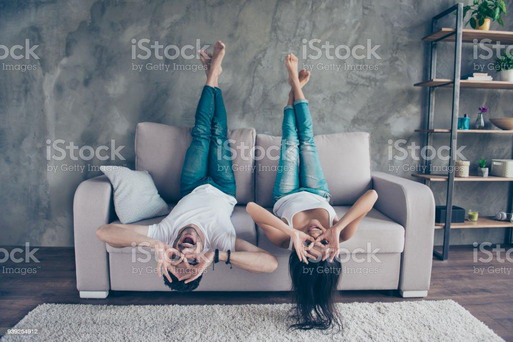 Pareja divertida con gafas gesticular es acostado boca abajo en el sofá en casa. Son tan alegres, divertirse juntos, loco, hermano y hermana - foto de stock