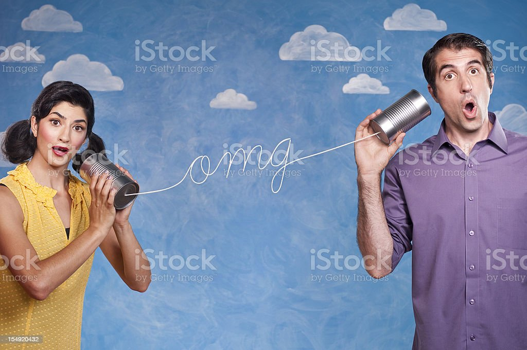"Funny Couple With Tin Can Telephones Young funny couple speaking on tin can telephones, The string spells ""OMG"", ""oh my god"". This shot was done in the studio in front of a painted cloud background. Activity Stock Photo"
