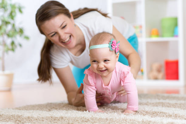 Funny crawling baby girl with mother stock photo
