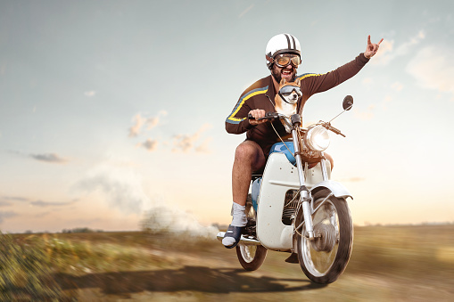 A man with a vintage helmet and goggles is riding a retro style moped. His left hand is raised forming devil horns. His pet dog is placed inside his jacket also wearing goggles. Motion blurred background with copy space.