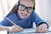 istock Funny curious clever girl writing and smiling 875554446