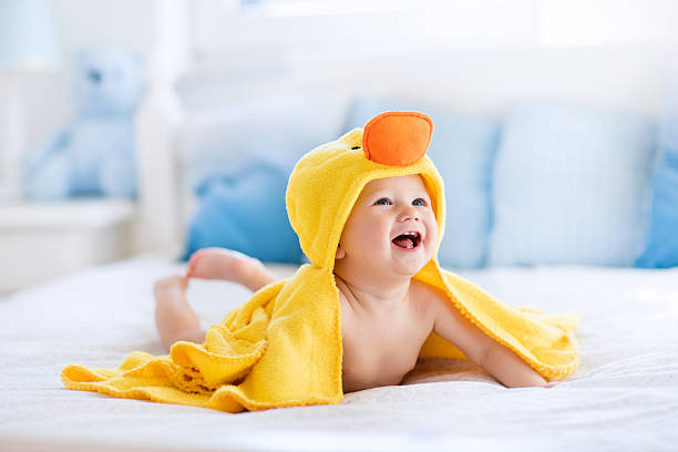 Funny cute baby after bath in yellow duck towel stock photo