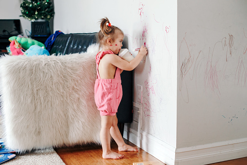 Funny cute baby girl drawing with marker on wall at home. Toddler girl child with milk bottle playing at home. Authentic candid childhood lifestyle moment. Young artist painting on wall in living room