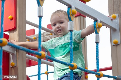 656743520istockphoto Funny cute blond baby boy plays on the playground, smiling. The emotion of happiness, fun, joy. 1146759683