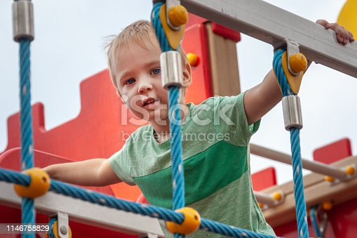 656743520istockphoto Funny cute caucasian blond baby boy plays on the children playground. The emotion of happiness, fun, joy. 1146758829