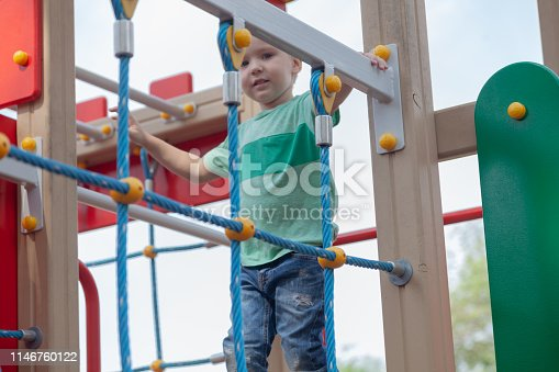 656743520istockphoto Funny cute caucasian blond baby boy plays on the children playground. The emotion of happiness, fun, joy. 1146760122