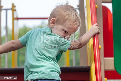 656743520istockphoto Funny cute caucasian blond baby boy plays on the playground, climbing upstairs. The emotion of happiness, fun, joy. 1146754103