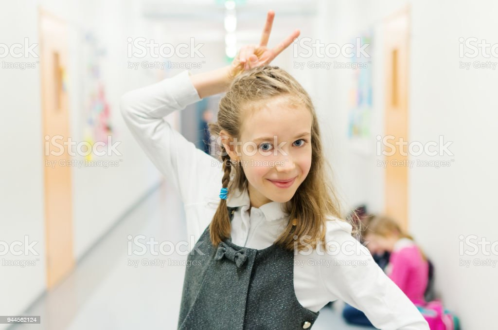 Funny cute girl at break time in school. stock photo