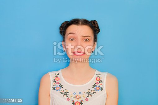 Funny cute girl on a blue studio background. Bright emotional female portrait. Failed grimace face.