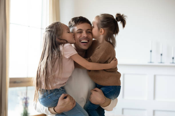 Funny cute small daughters kiss happy daddy on cheeks stock photo