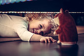 Funny cute smiling child playing hide and seek under the bed with toy hamster in vintage style