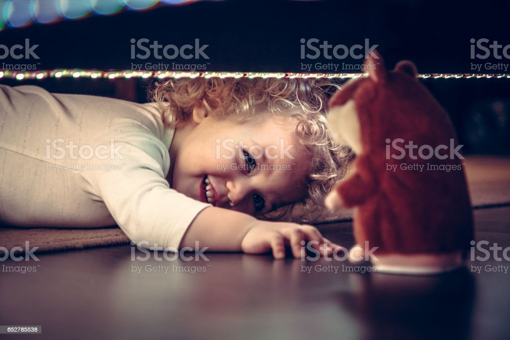 Funny cute smiling baby playing hide and seek under the bed with toy hamster in vintage style - foto de acervo