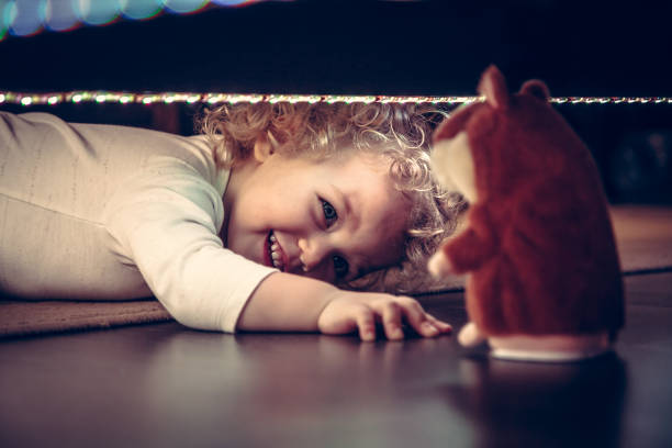 Funny cute smiling baby playing hide and seek under the bed with toy hamster in vintage style Funny cute smiling child playing hide and seek under the bed with toy hamster in vintage style hide and seek stock pictures, royalty-free photos & images