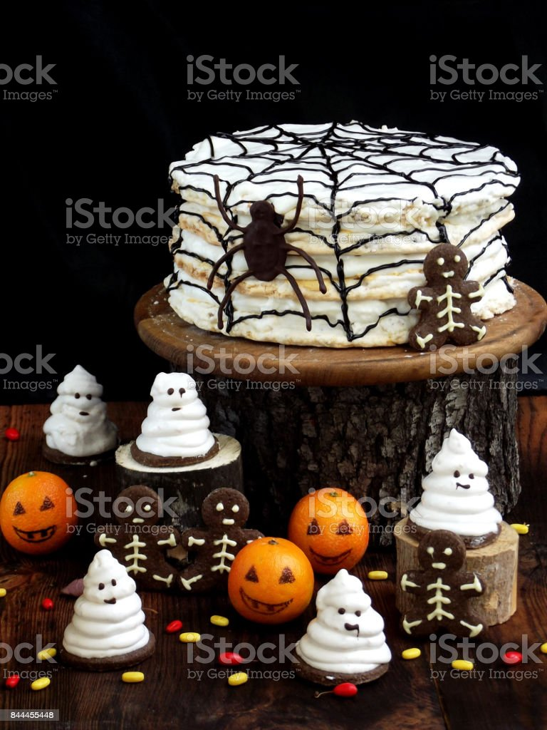 Funny delicious composition for Halloween with cake, biscuits, marshmallow and mandarins on the table. Sweets in the form of ghosts, skeletons, spiders and pumpkin jack stock photo
