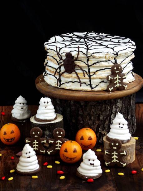 lustige köstliche komposition für halloween mit kuchen, kekse, eibisch und mandarinen auf dem tisch. süßigkeiten in form von geister, skelette, spinnen und kürbis jack - halloween party lebensmittel stock-fotos und bilder