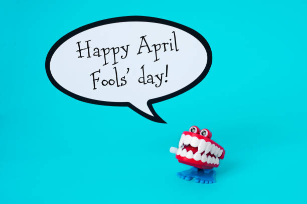 funny denture and text happy april fools day a funny denture and the text happy april fools day in a speech balloon, on a blue background april fools day stock pictures, royalty-free photos & images