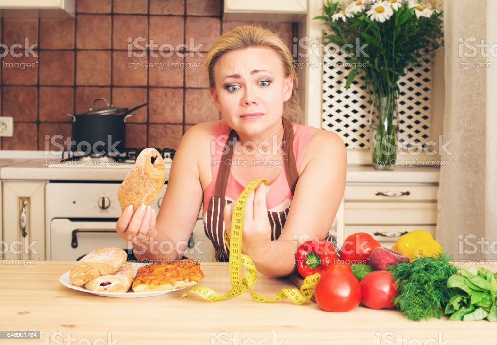 Funny dieting woman housewife choosing between healthy and fast food stock photo