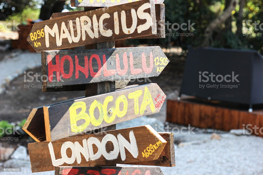 Funny direction signpost with distance to many different cities stock photo