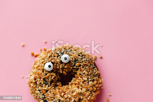 Funny shock face chocolate peanut donut on a pastel pink background, creative minimal Halloween concept with copy space
