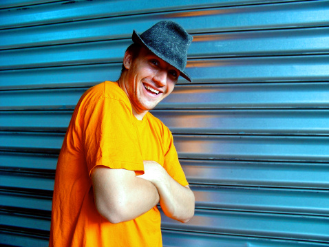 Funny young man standing against a blue metal wall. With crossed arms and happy smile.