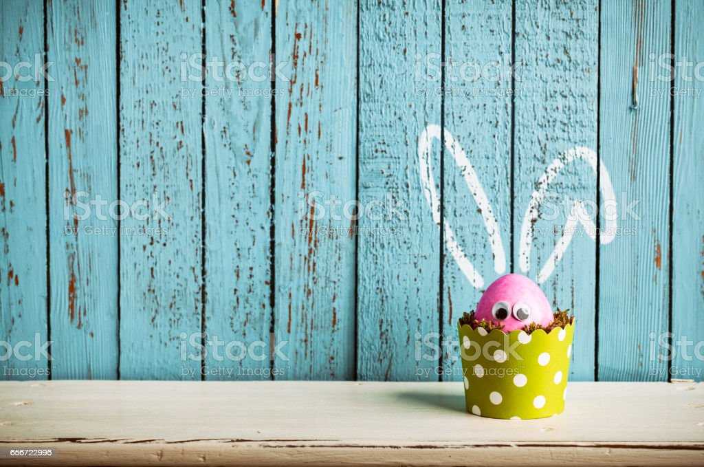 Photography of a pink easter egg in a dotted green cake pan.