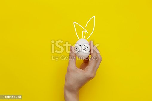 Woman holding white egg on colored background