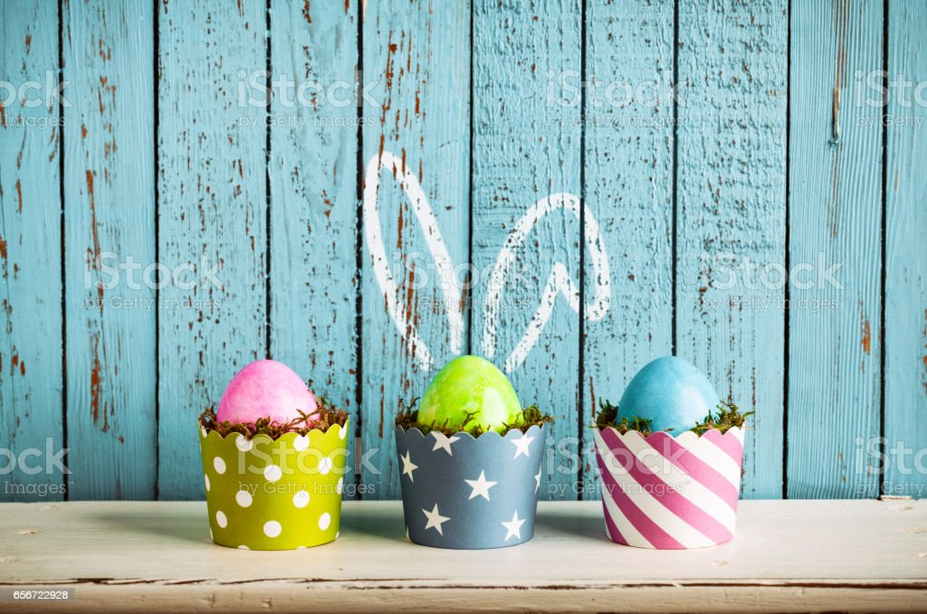 Photography multi colored easter eggs in cake pans with moss.