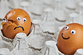 istock Funny egg and sad cracked egg in paper egg tray 1294465417