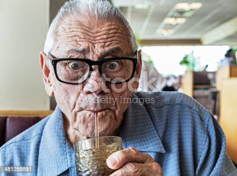 An humorous elderly man with a wide-eyed, surprised facial expression is drinking water - or something even better - through a drinking straw.