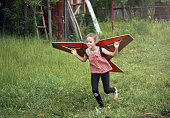 Cute blond girl is playing with the toy hang glider wings. She is running on a lawn and imagining herself in flight. The girl is smiling looking ahead. Outdoor shooting at a back yard of country cottage at summer day