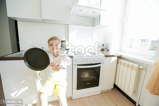 488109116 istock photo funny European little boy chef dancing,Happy weekend, boy wants to make pancakes, but the frying pan are too gay, he decided to have fun holding wooden spoons in his hands, having fun while cooking 1130690755