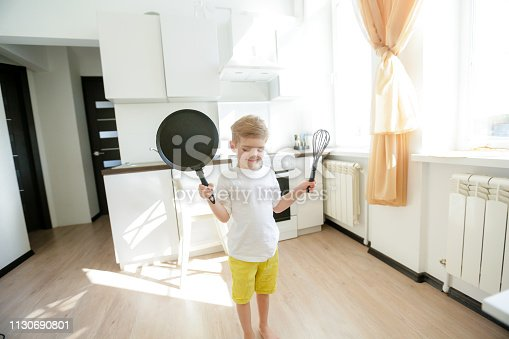 488109116 istock photo funny European little boy chef dancing,Happy weekend, boy wants to make pancakes, but the frying pan are too gay, he decided to have fun holding wooden spoons in his hands, having fun while cooking 1130690801