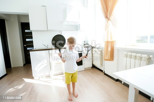 488109116istockphoto funny European little boy chef dancing,Happy weekend, boy wants to make pancakes, but the frying pan are too gay, he decided to have fun holding wooden spoons in his hands, having fun while cooking 1130691048
